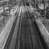 Perspektivenansicht von Eisenbahnlinien mit obenliegenden Linien nahe bei einer Plattform lizenzfreies stockfoto