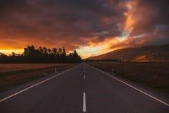 Perspektivenfahrbahn im Sonnenunterganghimmel stockfotos