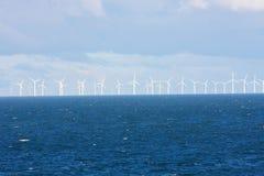 Perspektivenlinie von Ozeanwindmühlen mit dunklem Wasser und Himmel Stockbild