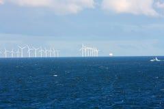Perspektivenlinie von Ozeanwindmühlen mit dunklem Wasser und Himmel Lizenzfreies Stockbild