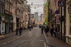 Perspektivgatasikt av byggnader, folk och trafik på en jul dekorerad gata i Amsterdam royaltyfria bilder