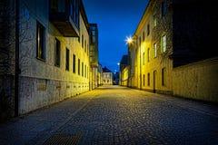 Perspektivnattsikt av en tom stads- kullerstengata med lynniga ljus Royaltyfria Bilder