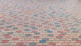 Perspektivsikt av den färgrika vägen för tegelstenstengata Trottoar trottoartexturbakgrund Fotografering för Bildbyråer