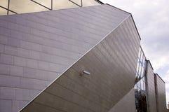 Perspektivsikt av den moderna byggnadsfasaden med den hållande ögonen på kameran på väggen Arkivfoto