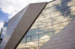 Perspektivsikt av den moderna byggnadsfasaden med molnreflexioner på fönstren Royaltyfri Foto