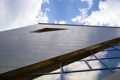 Perspektivsikt av den moderna byggnadsfasaden med molnreflexioner på fönstren Arkivfoton