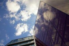 Perspektivsikt av den moderna byggnadsfasaden med molnreflexioner på fönstren Royaltyfri Fotografi