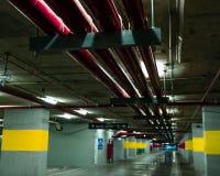 Perspektivsikt av den tomma inomhus bilparkeringsplatsen på gallerian Konkret parkeringsgarage för tunnelbana med den öppna lampa Royaltyfri Bild