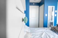 Perspektivsikt av ett sovrum som visar en skänkknopp, blåa målade väggar, vita brytningar och en säng utan filtar, med smutsigt, arkivbild