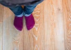 Perspektivsikt av fot för unge` ett s med lilasockor och blå jean Arkivfoto