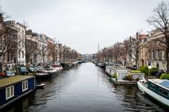 Perspektivstadssikt av byggnader och många husbåtar på en kanal i Amsterdam royaltyfri bild