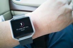 Perspektywicznego widoku osoby czytania zegarek z krokami i kierowym tropicielem podczas gdy jadący samochód Obrazy Stock