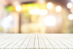 Perspektywiczny drewniany stół na wierzchołku nad plamy sklep z kawą tłem obrazy stock
