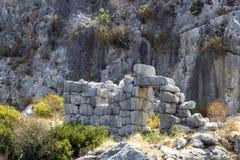 Perspektywiczny krótkopęd dziejowa kamieniarstwo kamiennej ściany ruina należy Lycian ludzie przy morzem śródziemnomorskim obraz royalty free