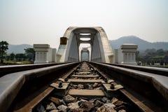 Perspektywiczny widok biały linia kolejowa most z górami i niebieskiego nieba tłem fotografia royalty free