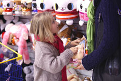 Persuaded to purchase toys. Mother and daughter in a children's toy departmant, make a purchase Royalty Free Stock Photography