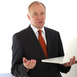 Persuasive businessman holding laptop. Persuasive businessman talking and gesturing to the camera holding an open laptop balanced on his arm Stock Photos