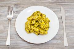 Perte de poids amincissant le concept affamé suivant un régime de femme de centimètre Concept de suivre un régime Le plat avec le Photographie stock libre de droits