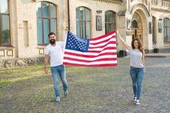 Pertença à nação americana Cidadãos felizes que comemoram o Dia da Independência Cidadãos americanos que guardam a bandeira nacio imagens de stock