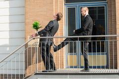 Pertenencia de Kicking Employee With del hombre de negocios fuera de la oficina fotografía de archivo libre de regalías