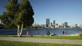 Perth Mill Point. Perth Downtown cityscape with skyscrapers reflecting on the Swan River from Mill point in Western Australia. Perth Skyline with people fishing stock video footage