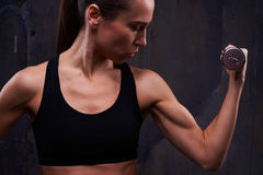 Pertinacious muscular fitness woman with dumbbell pumping up bic Stock Photos