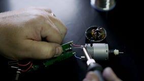 Perto acima, as mãos mestras reparam o dispositivo eletrónico com ferro de solda, movimento lento filme