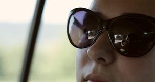 Perto acima da cara da mulher nos óculos de sol no carro vídeos de arquivo