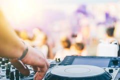 Perto acima da mão do DJ que joga a música na plataforma giratória em um festival do partido da praia - retrato do áudio do mistu fotografia de stock royalty free