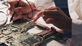 Perto acima das mãos do coordenador usando o verificador do multímetro para verificar o cartão-matriz no laboratório filme