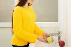 Perto acima das m?os das mulheres que lavam a ma?? verde no dissipador imagens de stock