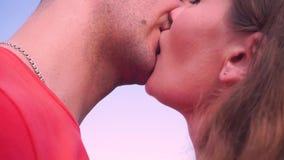Perto acima, homem novo e beijo da mulher delicadamente contra o céu video estoque