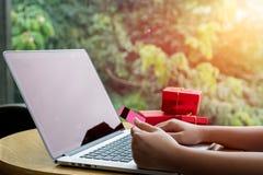 Perto acima, teclado de datilografia do portátil da mulher asiática nova e guardar o cartão de crédito na cafetaria com compra ou foto de stock