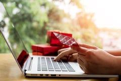 Perto acima, teclado de datilografia do portátil da mulher asiática nova e guardar o cartão de crédito na cafetaria com compra ou imagem de stock royalty free