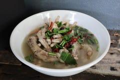 Perto acima, Tom Yum, pé de galinha, alimento tailandês picante, ervas no copo, o fundo de madeira velho imagens de stock
