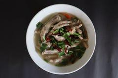 Perto acima, Tom Yum, pé de galinha, alimento tailandês picante, pôs ervas no copo, fundo preto fotos de stock