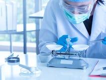 Perto acima, um químico asiático que usa a escala mecânica imagens de stock