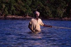 Perto de Port Blair, ilhas de Andaman, Índia, cerca do outubro de 2002: Pescador que puxa a rede de pesca do oceano imagens de stock