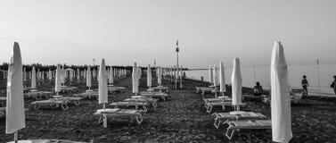 Perto dos povos preto e branco dos guarda-chuvas de praia do mar imagem de stock