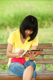 Pertty Asian young girl on tablet. Pertty Asian young girl on tablet computer outside Royalty Free Stock Photography