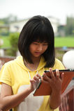 Pertty Asian young girl on tablet . Pertty Asian young girl on tablet computer outside Royalty Free Stock Photos