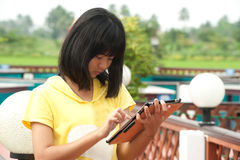 Pertty Asian young girl on tablet . Pertty Asian young girl on tablet computer outside Stock Photos