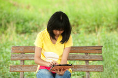 Pertty Asian young girl on tablet . Pertty Asian young girl on tablet computer outside Stock Image