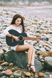 Pertty musician. Lovely Asian woman sitting on beach and playing guitar Stock Images