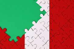 Peru flag is depicted on a completed jigsaw puzzle with free green copy space on the left side.  stock images