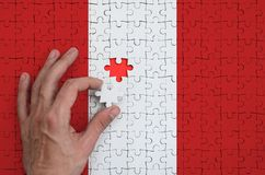 Peru flag is depicted on a puzzle, which the man`s hand completes to fold.  royalty free stock photography
