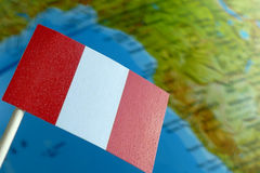 Peru flag with a globe map as a background. Macro stock images