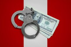 Peru flag with handcuffs and a bundle of dollars. Currency corruption in the country. Financial crimes.  royalty free stock photo