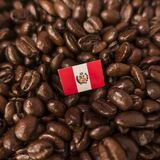 A Peru flag placed over roasted coffee beans.  stock image