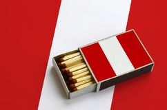 Peru flag is shown in an open matchbox, which is filled with matches and lies on a large flag.  stock photography